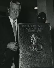 "Pee Wee King holds his plaque after his induction into the Country Music Hall of Fame in 1974. King, born Julius Frank Anthony Kuczynski in Milwaukee, was an important figure in country music starting in the late 1930s; Ken Burns' new documentary series ""Country Music"" puts a spotlight on his contributions. This photo was in the Jan. 12, 1975, Milwaukee Journal."