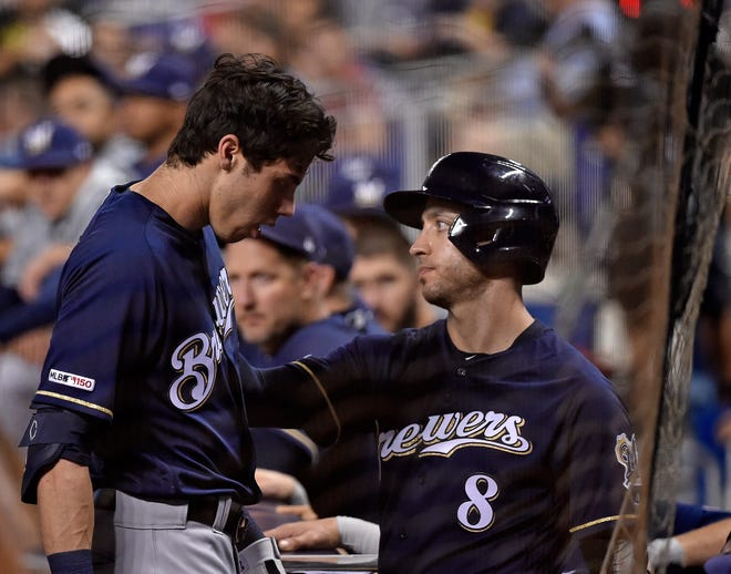 Christian Yelich gets a conciliatory pat of the shoulder from teammate Ryan Braun as the Brewers rightfielder leaves the game after fouling a ball off his right knee in the first inning.