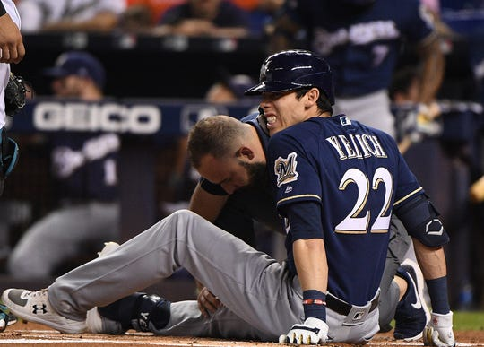 Christian Yelich grimaces in pain as he's checked out by the Brewers' team trainer after he fractured his right kneecap after fouling a pitch off it in the first inning.