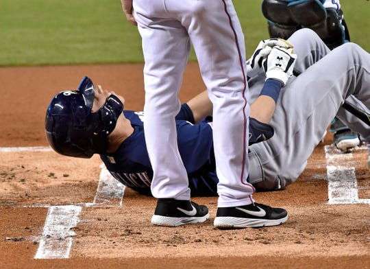 Christian Yelich lays on the ground in pain after fouling a pitch off his right knee in the first inning. The Brewers star was forced to leave the game with an apparent injury to the knee.