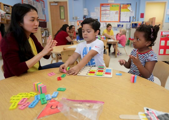 Preschoolers Marissa Wilkes, right, and Noel Carteno work on counting activities with teacher Visaria Wang at El Hogar del Niño, a Head Start center on South Loomis Street in Chicago.