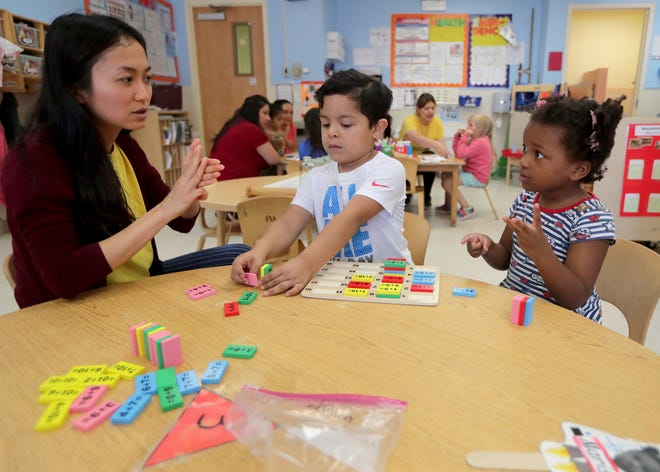 Preschoolers Marissa Wilkes, far right, and Noel Carteno work on counting activities with teacher, Visaria Wang at El Hogar del Niño, a child care center on South Loomis Street in Chicago. El Hogar del Niño is the site of multiple studies that found that sending text messages to parents resulted in higher attendance and as well as parents reading more to their preschool-aged children. High-quality child care is seen as a solution to childhood trauma.