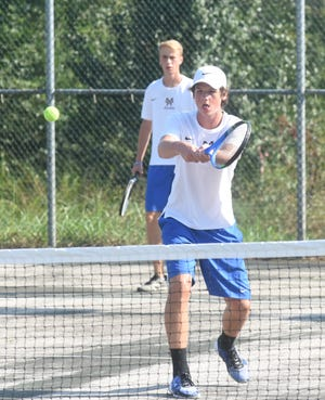 Mountain Home's Cooper Oxford returns a shot as doubles teammate Jeff Hodges looks on during recent action.