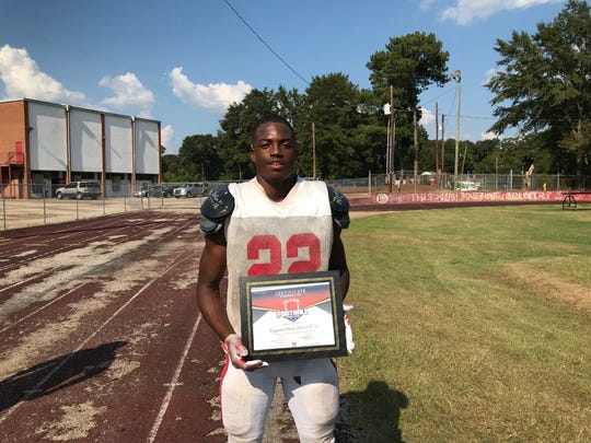 Robert E. Lee running back Reginald Davis holds his ASE Credit Union Player of the Week award.