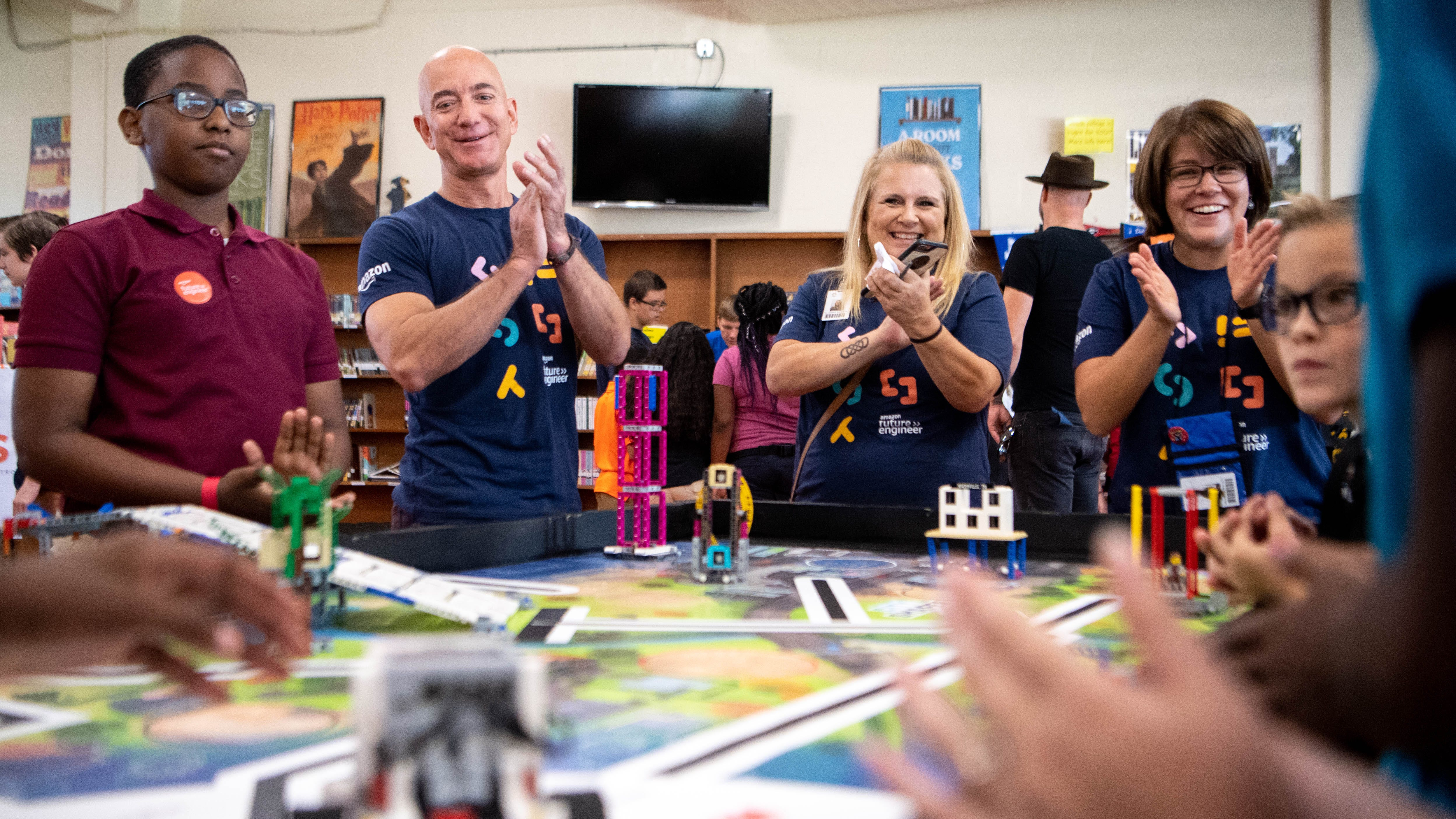 Amazon CEO Jeff Bezos applauds as students work with a robot at Madison Middle School Wednesday, September 11, 2019 in Nashville, Tenn.