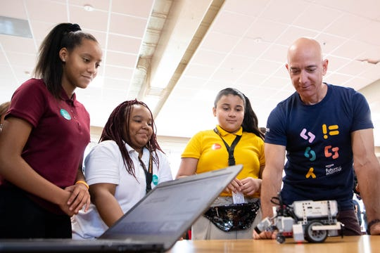 Amazon CEO Jeff Bezos watches as Mackenzie Beck, 8th grade, Courmori Choate, 5th grade, and Itzel Gomez, 5th grade, from left, work with a robot at Madison Middle School Wednesday, Sept. 11, 2019, in Nashville, Tenn.