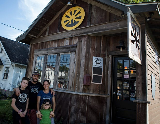 Jonny Stone and his wife, Heidi, stand in front of their vegan taco restaurant in Alexandria, The Village Taco Shop with two of their children, Keon and River.