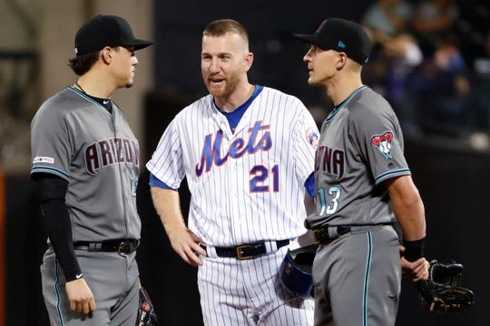 Arizona Diamondbacks second baseman Wilmer Flores, left, chats with New York Mets' Todd Frazier (21) and Diamondbacks shortstop Nick Ahmed (13) during a video review of a play at the plate in the second inning of a baseball game Tuesday, Sept. 10, 2019, in New York. Flores is a former Met and played on the team with Frazier.