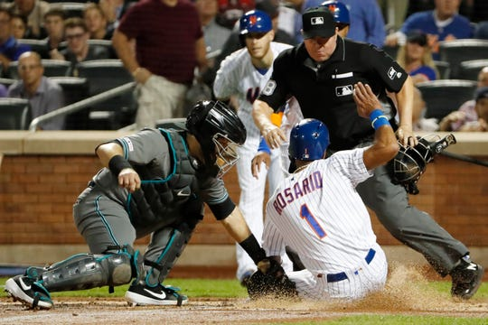 New York Mets' Amed Rosario (1) is safe at the plate as Arizona Diamondbacks catcher Alex Avila, left, tries to make the tag, with home plate umpire Doug Eddings watching on Todd Frazier's second-inning, two-run double in a baseball game Tuesday, Sept. 10, 2019, in New York. The play was reviewed and the call upheld.