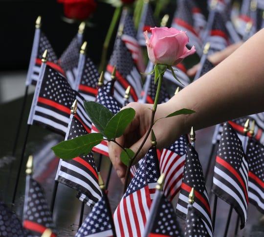 Flores y bandera en honor a los caídos del 9-11.