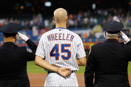 New York Mets pitcher Zack Wheeler (45) stands between two uniformed officers during a Sept. 11, 2001. tribute before the team's baseball game against the Arizona Diamondbacks on Wednesday, Sept. 11, 2019, in New York. (AP Photo/Kathy Willens)
