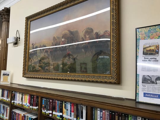 "A replica of the 1863 Emanuel Leutze painting, ""Indians Attacking a Wagon Train"" hangs in the Dover library after the original was sold for more than $4 million."