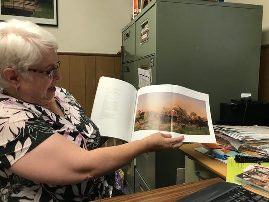"Dover library Director Diane Sebastian shows a photo of ""Indians Attacking a Wagon Train"" a painting by Emanuel Leutze that hung in the reading room for almost 60 years.  It was sold for more than $4 million."