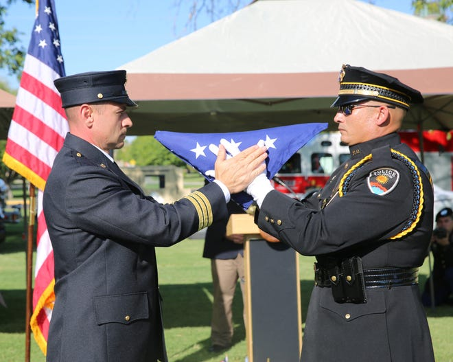 New Mexico State University Fire Department Captain John Guerin and Las Cruces Police Department officer Daniel Lopez, fold the September 11, 2001, memorial flag during the Patriot Day ceremony held at Horseshoe Park in Las Cruces, Wednesday, Sept. 11, 2019.
