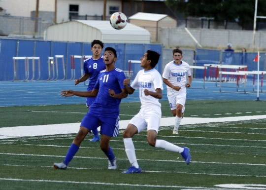 Carlsbad's Leonel Martinez (11) battles a Goddard player for possession during Tuesday's game at Ralph Bowyer Caveman Stadium. Carlsbad won, 5-0.