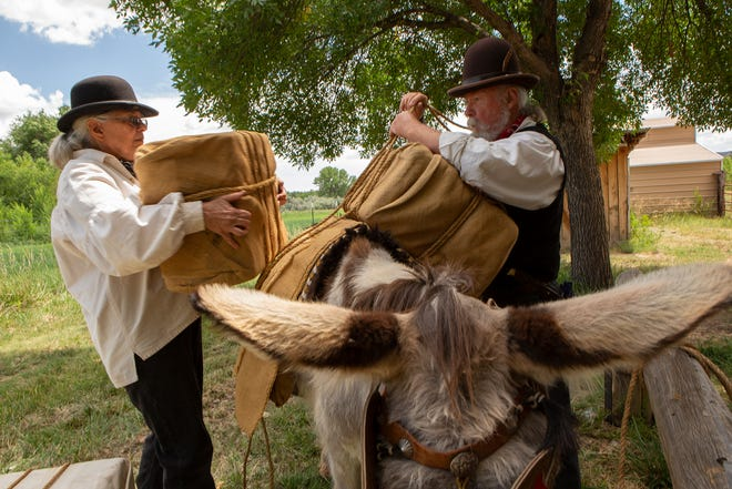 Pat and Ron Rundstrom load cargo on a burro using the aparejo saddle pack system they will be demonstrating this weekend during the Old Spanish Trail Festival at Aztec Ruins National Monument.
