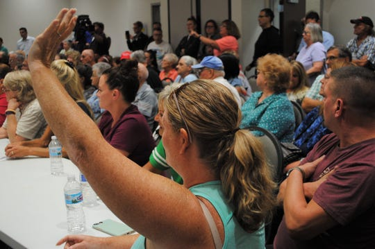 A resident raises her hand in the standing-room-only meeting room on Sept. 10