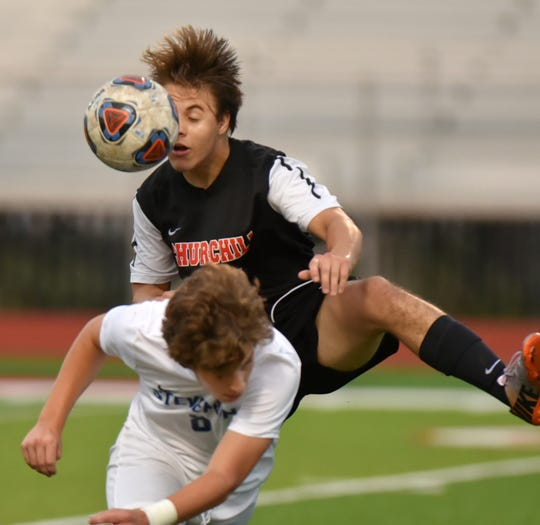 Livonia Churchill Charger Garrett Englehart goes up over Stevenson's Reece Brown to play the ball.