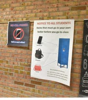 Posters announcing the new procedure for no backpacks or cell phones in classrooms at Westland's Stevenson Middle School line its hallways.