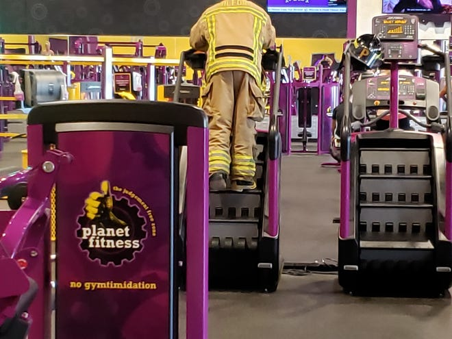 Drew Burrow, a Milford firefighter, climbs stairs in full gear at Planet Fitness on Sept. 11, to honor those who lost their lives on this date 18 years ago in the terrorist attacks on the World Trade Center.