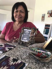 Treasure Welmas poses with a picture of her father at her home on the Cabazon Band of Mission Indians reservation on Aug. 14, 2019.