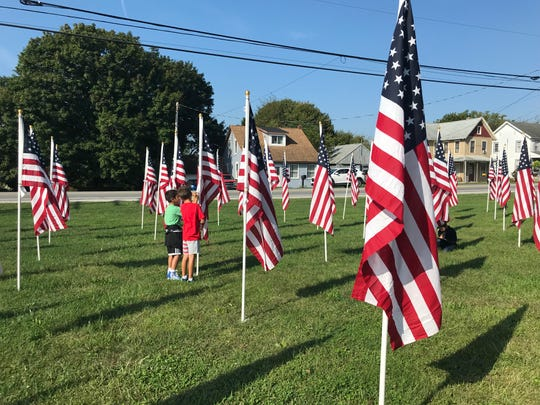 Third-graders in Wendy Currey's class read the name tags at the flag display at West Manheim Elementary School on Wednesday, Sept. 11, 2019.