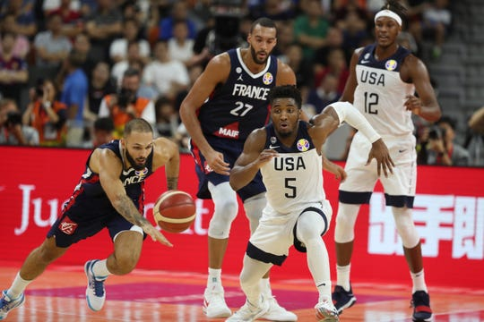 United States' Donovan Mitchell (5) chases down a loose ball ahead of his Utah Jazz teammate, France's Rudy Gobert (27), during the United States 89-79 loss to France in the quarterfinals of the FIBA Basketball World Cup on Sept. 11, 2019.