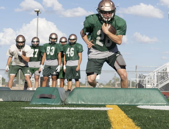 Campo Verde High School, running back, Caden Calloway, on right, and his brother Connor Calloway, far left in white jersey, during the practice at their school.