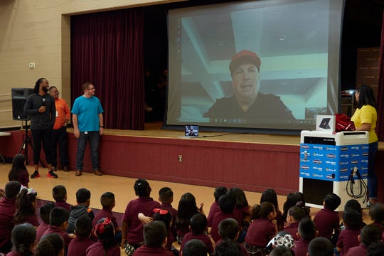 Country singer Garth Brooks addresses students at Academia Del Pueblo, a charter school in Phoenix, over a livestream. Standing next to the screen is Arizona Cardinals wide receiver Larry Fitzgerald.