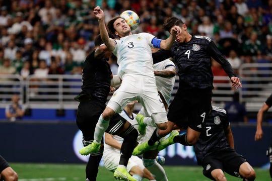 Nicolás Tagliafico de Argentina pelea la bola con dos jugadores mexicanos.