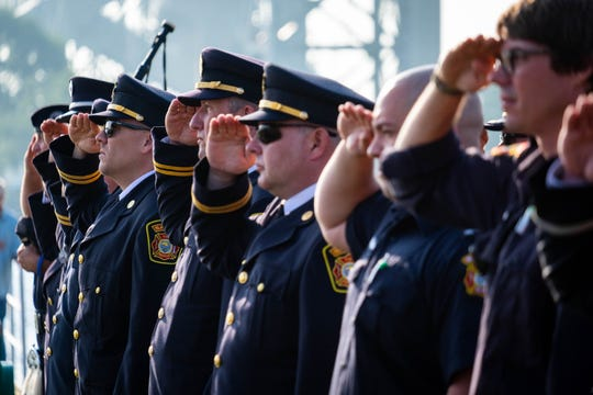First responders hold a salute as the National Anthem is sang by the Schubert Male Chorus during the annual 9/11 memorial ceremony Wednesday, Sept. 11, 2019, at the International Flag Plaza in Port Huron.