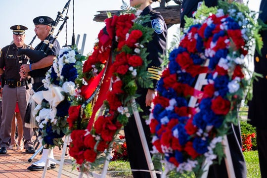 Marysville Police Officer Jim Disser plays 'Amazing Grace' on bagpipes while representatives from the Port Huron police and fire departments and Tri-Hospital EMS present three wreaths during the annual 9/11 memorial ceremony Wednesday, Sept. 11, 2019, at the International Flag Plaza in Port Huron.