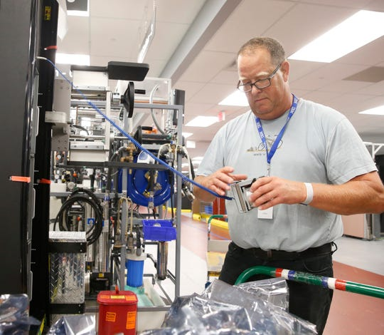 Manufacturing specialist Bill Bornstein installs fan units into a Z15 server on the production line at IBM's plant in Poughkeepsie on September 10, 2019.