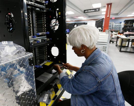 Manufacturing specialist Dayveena Holman installs components into a Z15 server on the production line at IBM's plant in Poughkeepsie on September 10, 2019.