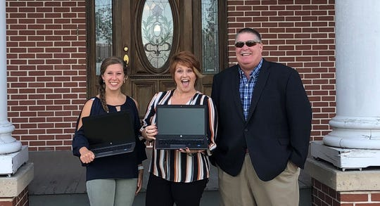 Nikki Martin, activities director for Monarch's Way and Carissa Martin, director of Monarch's Way, accept donated laptops from Jim Crowder, external affairs consultant for FirstEnergy/West Penn Power.