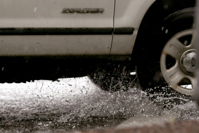 A car drives through a puddle as rain, with flash flooding in some parts, falls in Salem in September 2019.