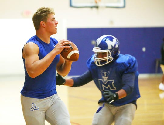 McNary High School quarterback Erik Barker throws short passes to his receivers during practice in the McNary gymnasium September 10, 2019. The team was forced to practice in the gym due to lightning and storms in the area.