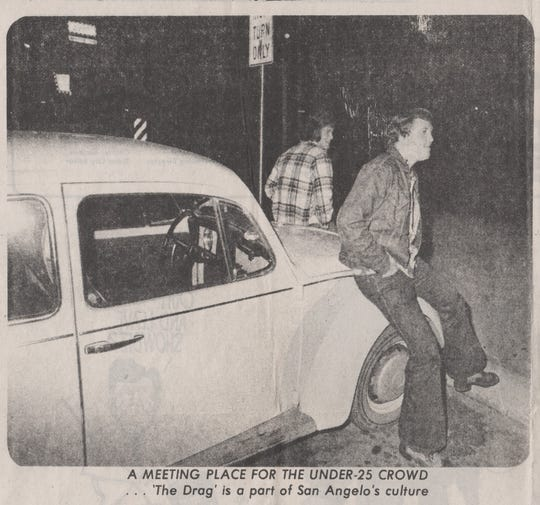 Friends lean on the hood  of a Volkswagen Beetle while watching cars go by on the Drag in San Angelo in this photograph from March of 1976.