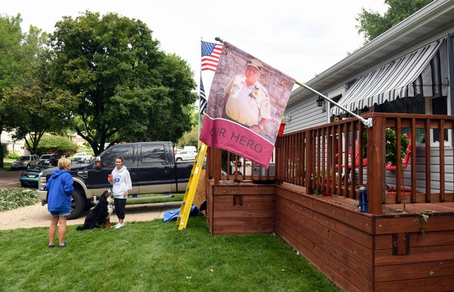 Lynette Johnson said that despite her deck being entirely covered in fallen tree limbs on Wednesday morning, September 11, the flag bearing the face of her late husband, Ron, remained fully intact.