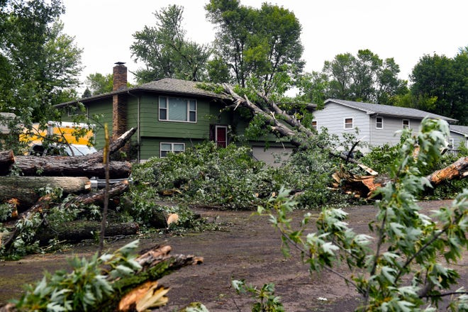 A tree lies on the roof of a home on Glendale Ave. in the aftermath of the tornado that ripped through the city on Wednesday, September 11, 2019.