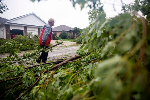 Jerome Kappes cuts trees in his neighborhood after a devastating tornado hit, Tuesday, Sept. 10, 2019.
