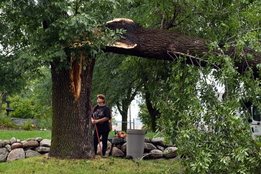 Susan Larson sweeps up debris from the sidewalk where a tree fell over during the tornado on Wednesday, September 11, 2019. Larson and Shawn Magee watched the tree crash down during the storm.