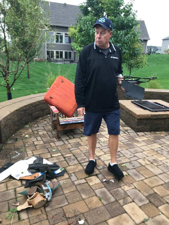 Sioux Falls resident Joe Sztapka picks up debris left in his backyard Wednesday, Sept. 11, 2019, after a tornado tore through southern Sioux Falls the night before.