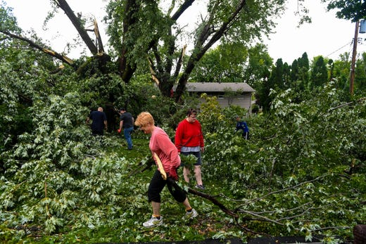 Neighbors join together to clear debris from Lindsey Waggoner's backyard after a tree fell and power lines were downed on Wednesday, September 11.