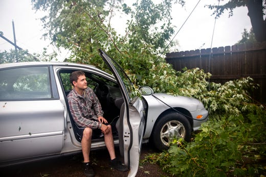 Hunter Heidebrecht sits in his tree limb covered car after a devastating tornado hit Sioux Falls on Tuesday, Sept. 10, 2019.