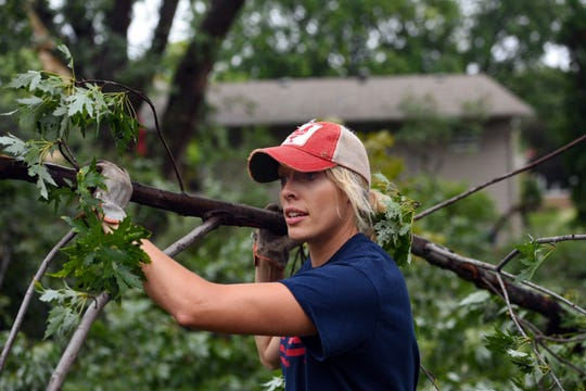 Lindsey Waggoner removes tree limbs from her yard in the aftermath of the tornado that ripped through the city on Wednesday, September 11, 2019.
