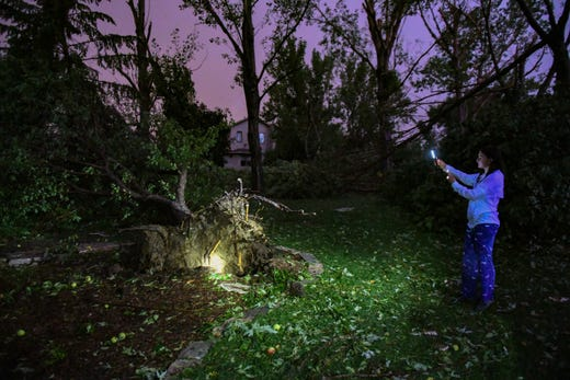 Sabrina Tynan looks at a tree that had been uprooted in her backyard by a tornado as lighting lights the sky in the distance on Tuesday night.
