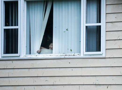 A girl looks out her window at the destruction left by a devastating tornado in Sioux Falls, Wednesday, Sept. 11, 2019.