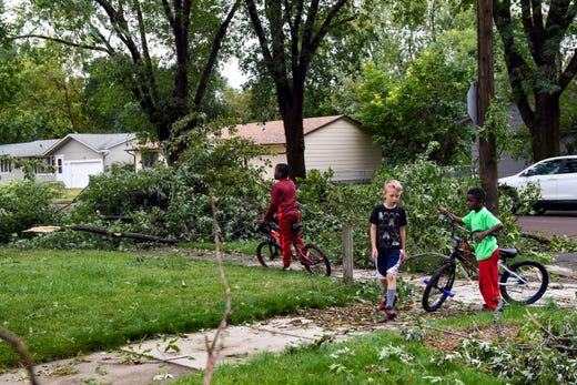 Children ride their bikes past the aftermath of the tornado that ripped through the city on Wednesday, September 11, 2019.