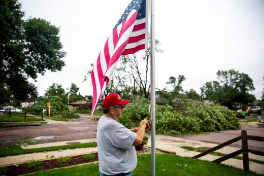 Dale Dorman raises the flag half-staff for 9/11 while crews in his neighborhood work to clean up debris after a devastating tornado hit in Sioux Falls, Wednesday, Sept. 11, 2019.